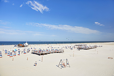 Vast beach with roofed wicker beach chairs on wooden plateaus and people celebrating the summer, Sankt Peter Ording, Schleswig Holstein, Germany, Europe