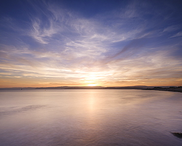 With interesting wispy clouds, the sun sets across the water from Exmouth, Devon, England, United Kingdom, Europe