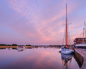 Turf Ferry and other boats moored on a mirror calm River Exe at Topsham, Devon, UK
