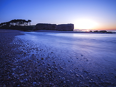 Sunrise behind the silhouetted cliff of Otter Head, where the River Otter meets the sea at Budleigh Salterton, Devon, England, United Kingdom, Europe