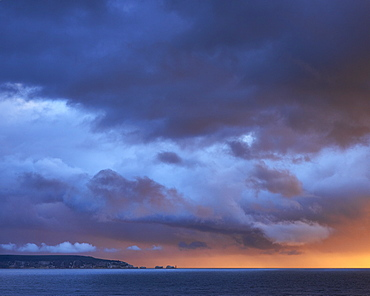 Dramatic sunset storm lighting and clouds over The Needles on the Isle of Wight, viewed from Milford-on-Sea, Hampshire, England, United Kingdom, Europe
