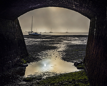 Boats on the Exe estuary in heavy fog viewed through an arch under the Exmouth to Penzance railway line, Starcross, Devon, England, United Kingdom, Europe