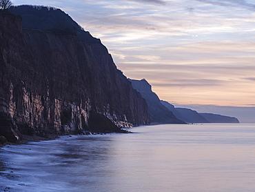 Soft glow of wet rock in pre-dawn twilight on the statuesque Jurassic Coast cliffs at Sidmouth, Devon, England, United Kingdom, Europe