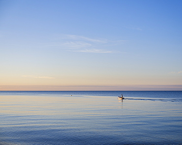 A fisherman leaves to tend his pots early in the morning on a calm sea at Budleigh Salterton, Devon, England, United Kingdom, Europe