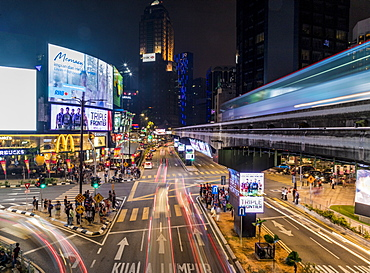 Night street scene in Bukit Bintang with a passing KL Monorail in Kuala Lumpur, Malaysia, Southeast Asia, Asia
