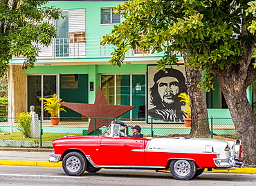 An old American car driving past a mural of Che Guevara, in Varadero, Cuba, West Indies, Central America