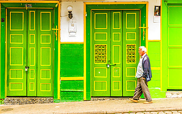 A local man walking past a typically colourful, preserved, colonial building in Jardin In Colombia.