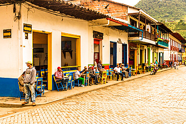 Local people socialising on the colourful main square, with its preserved, colourful, colonial buildings in Jardin, Colombia.