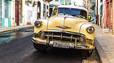 A vintage American car in a typical street in Havana, Cuba, West Indies, Caribbean, Central America