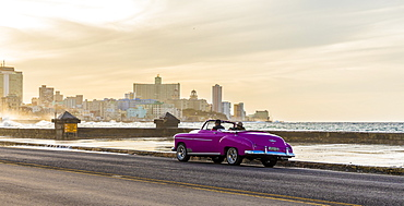 A vintage American car driving along the Malecon in Havana, Cuba, West Indies, Caribbean, Central America