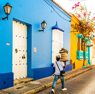 A street vendor walking past a colourful building in the old town in Cartagena, Colombia, South America