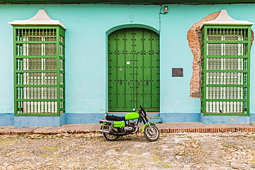 A motorbike in a typically colourful colonial street in Trinidad, Cuba, West Indies, Caribbean, Central America