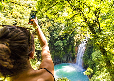 A tourist taking a picture of the Rio Celeste waterfall in Tenorio Volcano National Park, Costa Rica, Central America