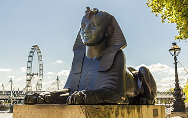 A sphinx on Victoria Embankment, with the London Eye in the background, London, England, United Kingdom, Europe
