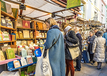 People at an antique book stall at Portobello Road market, in Notting Hill, London, England, United Kingdom, Europe