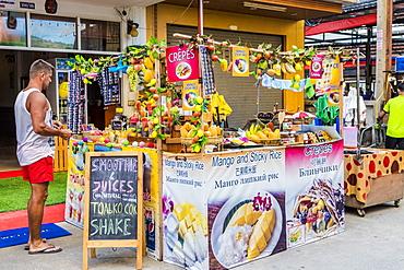 A tourist at a colourful pancake stall in Kata, Phuket, Thailand, Southeast Asia, Asia