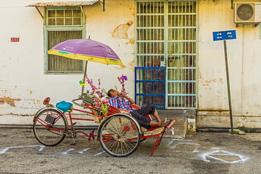 Local rickshaw (tuk tuk) driver in George Town, Penang Island, Malaysia, Southeast Asia, Asia