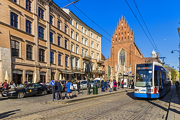 A tram outside the Dominican church in the medieval old town, UNESCO World Heritage Site, in Krakow, Poland, Europe