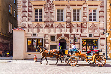A horse drawn carriage passing beautiful architecture in the old town, a UNESCO World Heritage site in Warsaw, Poland, Europe.