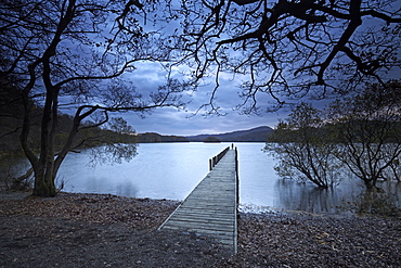 A solitary figure at dusk on Rigg Wood jetty, Coniston Water, Lake District National Park, UNESCO World Heritage Site, Cumbria, England, United Kingdom, Europe