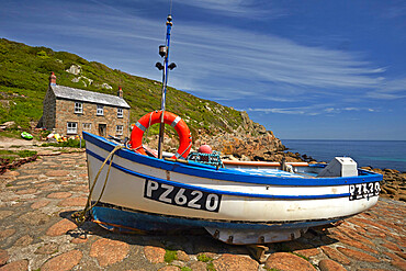 Fishing boat and cottage above the cobbled slipway at Penberth Cove, Cornwall, England, U.K.