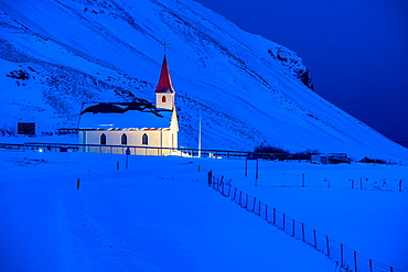 Floodlit church at dawn against snow covered mountains, near Vik, South Iceland, Iceland, Polar Regions