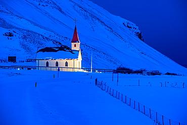 Floodlit church at dawn against snow covered mountains, near Vik, South Iceland, Iceland, Polar Regions