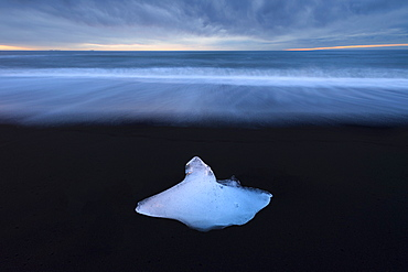 Glacier ice on black sand beach with waves washing up the beach, near Jokulsarlon, South Iceland, Iceland, Polar Regions