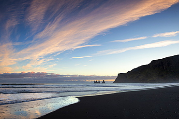 Looking towards the sea stacks of Reynisdrangar at sunset from the black volcanic sand beach at Vik i Myrdal, South Iceland, Iceland, Polar Regions