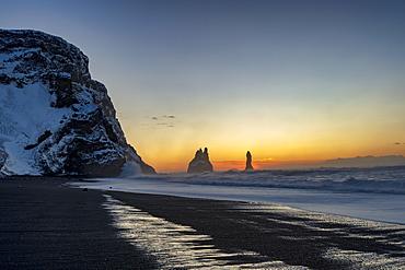 Rock stacks of Reynisdrangar at sunrise, from Halsanefs Hellir Beach near Vik, South Iceland, Iceland, Polar Regions