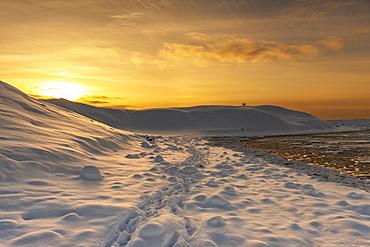 Tourists in winter standing on snow covered hill looking at Jokulsarlon lagoon, Jokulsarlon, South Iceland, Iceland, Polar Regions
