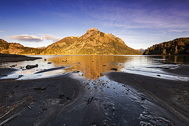 The black lava beach with reflected mountain, Bariloche, Patagonia, Argentina, South America
