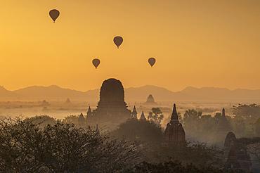 Atmospheric sunrise with ballons over Stupas in Bagan (Pagan), Bagan, Myanmar (Burma), Asia