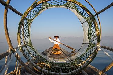 Intha leg rowing fisherman looking through fishing net, Inle Lake, Shan State, Myanmar (Burma), Asia