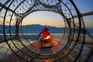 Intha leg rowing fisherman viewed through net on Inle Lake, Shan State, Myanmar (Burma), Asia