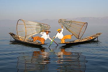 Two Intha leg rowing fisherman holding up fishing nets, Inle Lake, Shan State, Myanmar (Burma), Asia