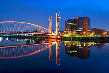 The Footbridge reflected in the River Irwell at night, Salford Quays, Manchester, England, United Kingdom, Europe