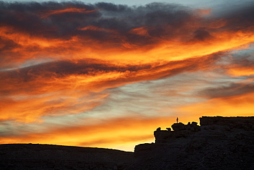 Lone figure on hill watching dramatic sunset, Ait Benhaddou, Morocco, North Africa, Africa