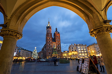 Saint Mary's Basilica at night framed with arch stonework in Market Square, UNESCO World Heritage Site, Krakow, Poland, Europe
