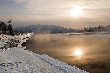 Reflected sun in Bow River in winter, Jasper, Canadian Rocky Mountains, Alberta, Canada, North America