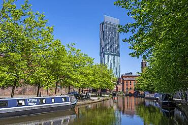 Moored canal boats at Castlefield Canal Basin with the Beetham Tower, Manchester, England, United Kingdom, Europe