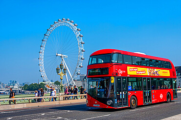 A red London bus travelling across Westminster Bridge with The London Eye, Westminster, London.