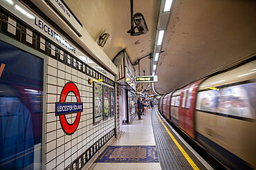 Leicester Square underground station with passing train, London