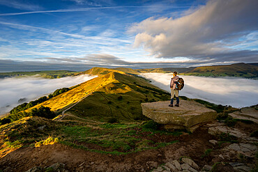 A male stood looking across The Great Ridge during a cloud inversion with view of Mam Tor, Hope Valley, Derbyshire