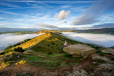 A walker sat looking across The Great Ridge and Mam Tor, Peak DIstrict, Derbyshire