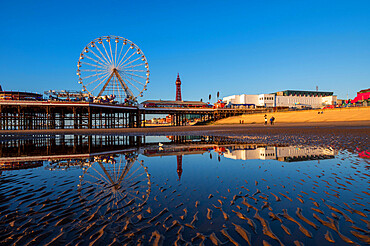 Blackpool beach with mirror reflections of the ferris wheel and Blackpool Tower, Blackpool, Lancashire
