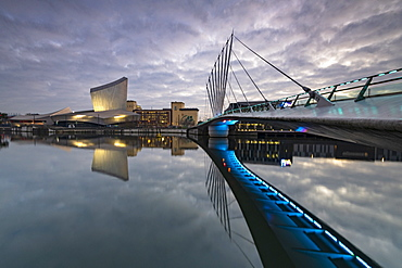 Pedestrian bridge over canal and Imperial War Museum North in Salford Quays, Manchester, England, United Kingdom, Europe