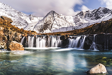 Cascades beneath the snow-covered Black Cuillin, Fairy Pools, Glen Brittle, Isle of Skye, Inner Hebrides, Highland, Scotland, United Kingdom, Europe