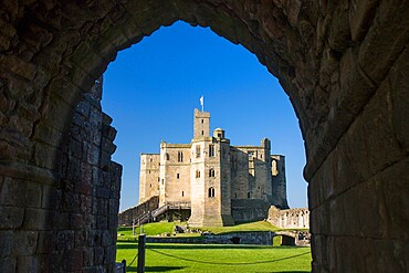 View through arch across lawns to the Great Tower of Warkworth Castle, Warkworth, Northumberland, England, United Kingdom, Europe