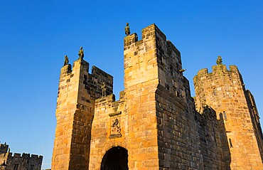 The medieval barbican and gatehouse of Alnwick Castle, sunset, Alnwick, Northumberland, England, United Kingdom, Europe